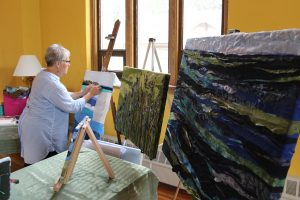 Pam Collins creating art in her home studio.